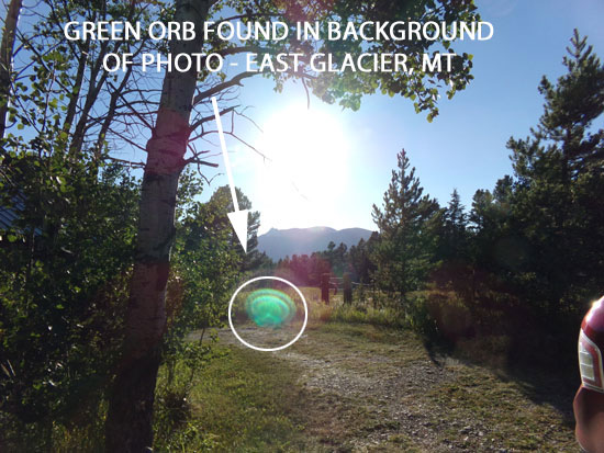 PHOTO OF GREEN ORB FOUND IN BACKGROUND OF PHOTO OF SUN.